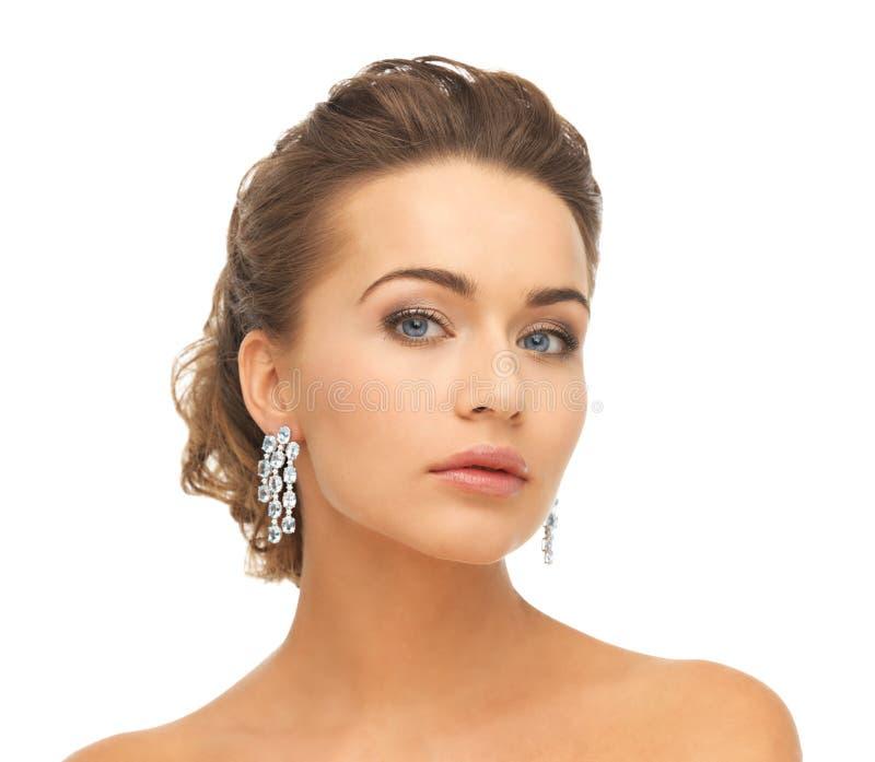 Kvinna som bär skinande diamantörhängen royaltyfri foto