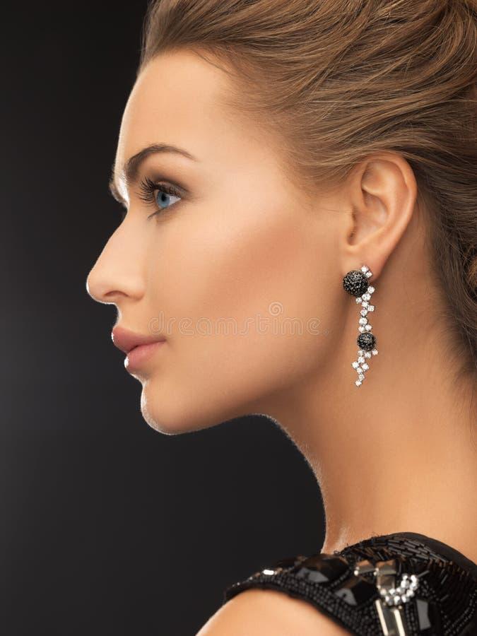 Kvinna som bär skinande diamantörhängen fotografering för bildbyråer