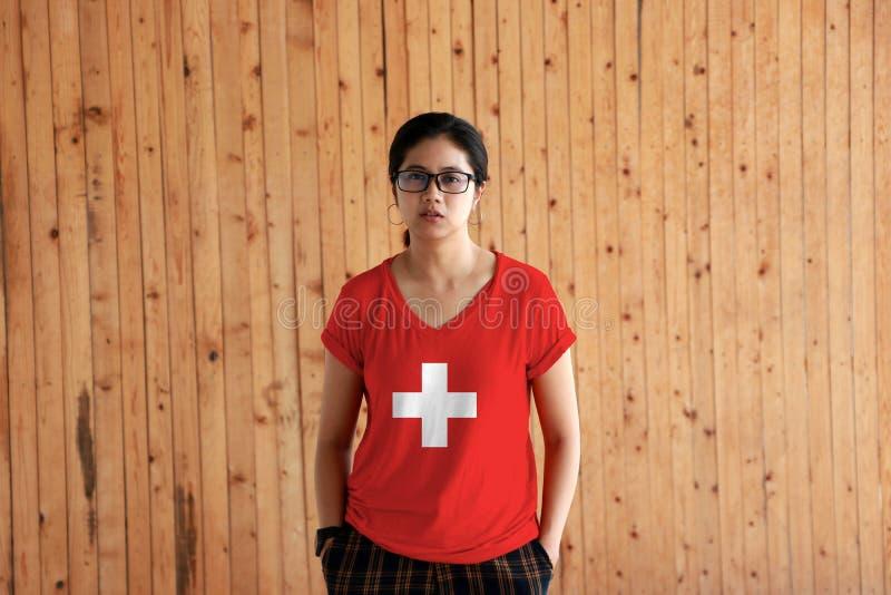 Kvinna som bär skjortan för Schweiz flaggafärg och står med två händer i flåsandefack på träväggbakgrunden royaltyfri fotografi