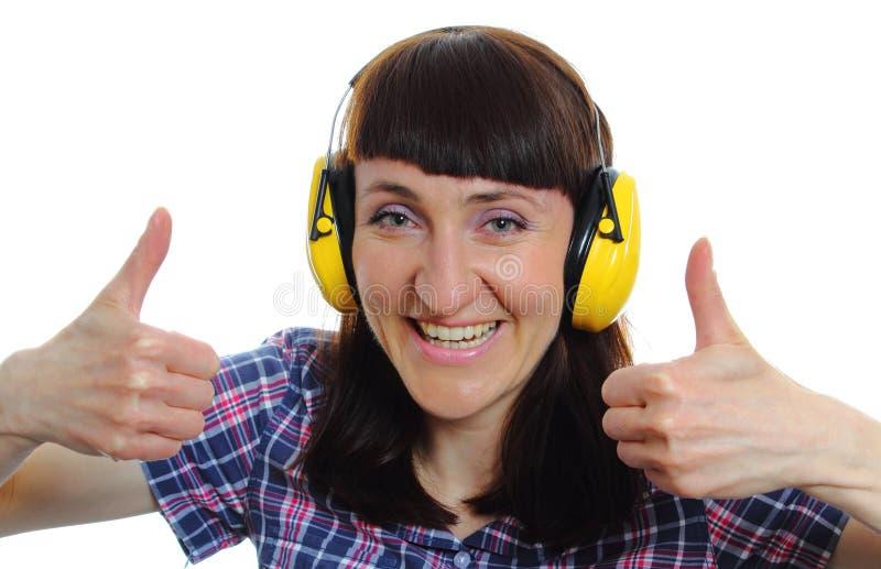 Kvinna som bär skyddande hörlurar och visar upp tummar arkivbild