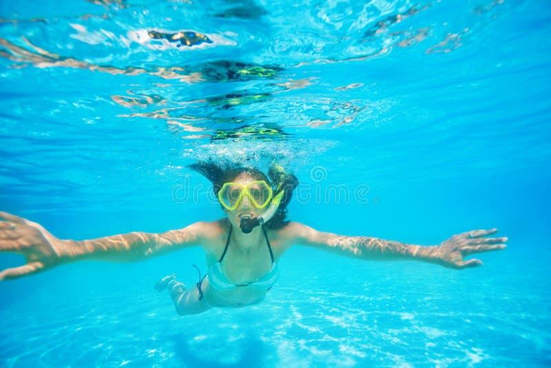 Kvinna som bär snorkla att simma för maskering som är undervattens- arkivfoton