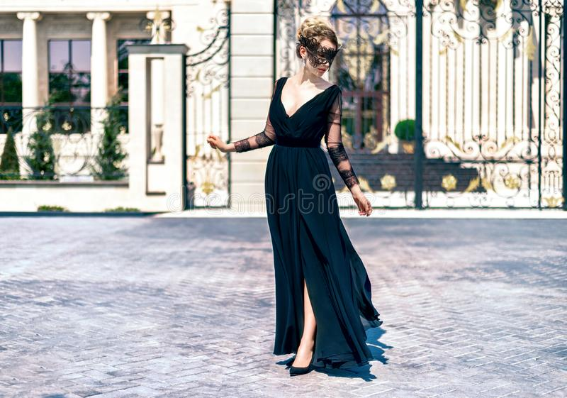 Kvinna som bär svart en utomhus- stående för maskering och för svart klänning Klassiska tappningblickar royaltyfria foton