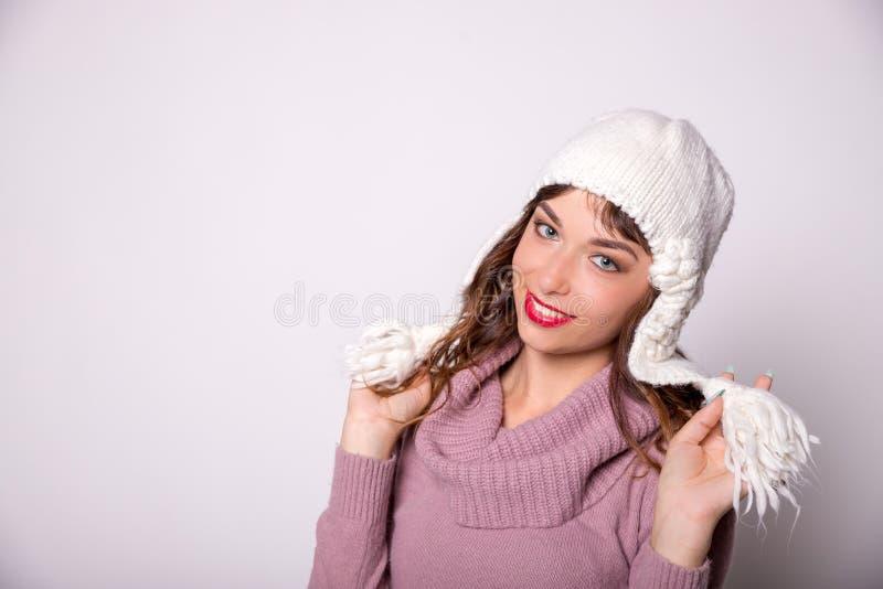 Kvinna som bär varm vinterkläder med den kniteed hatten isolerad le white för bakgrund flicka härlig vinterkvinna arkivbilder