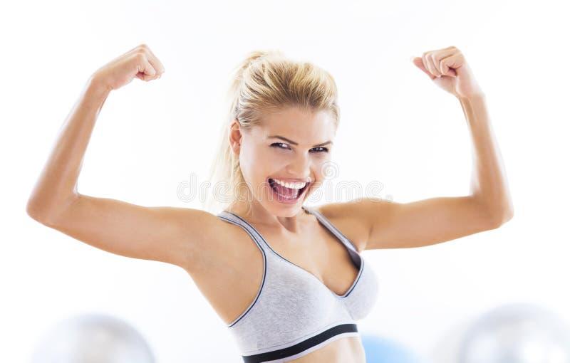 Kvinna som böjer biceps royaltyfria foton