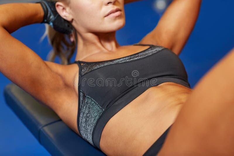 Kvinna som böjer buk- muskler på bänk i idrottshall royaltyfri foto