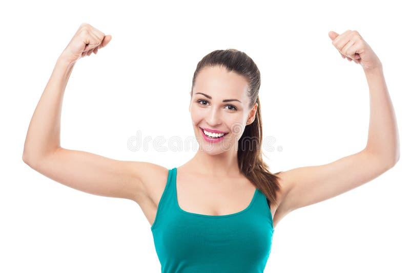 Kvinna som böjer muskler fotografering för bildbyråer