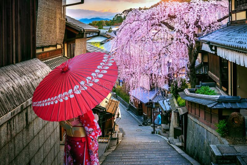 Kvinna som b?r den japanska traditionella kimonot som g?r p? det historiska Higashiyama omr?det i v?ren, Kyoto i Japan royaltyfri fotografi