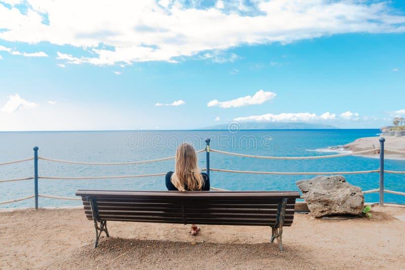 Kvinna som bara framme sitter på träbänken av havet royaltyfria bilder