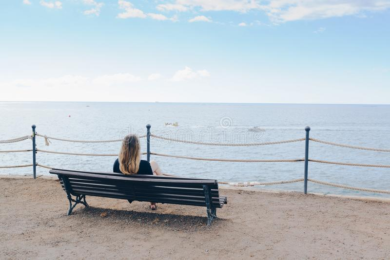 Kvinna som bara framme sitter på träbänken av havet royaltyfria foton