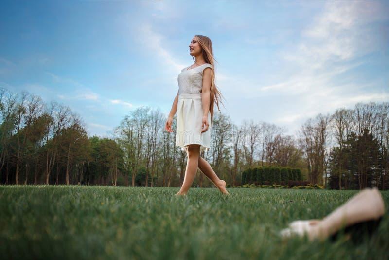 Kvinna som barfota går på grönt gräs Afton som går för hälsa arkivbild