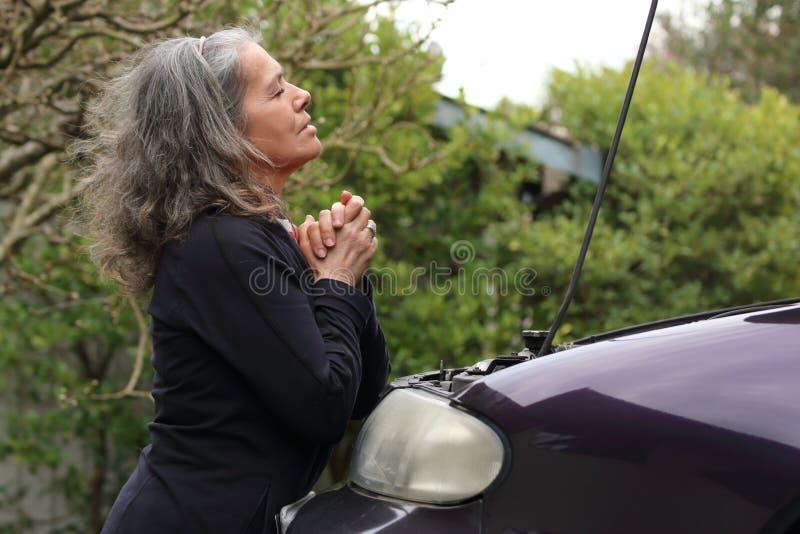 Kvinna som ber över hennes bil 2 arkivfoto