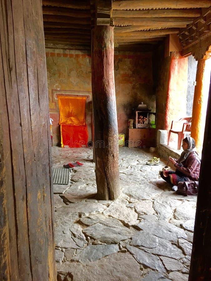 Kvinna som ber i en av templen på den Thiksay kloster i den Leh Ladakh regionen i Kashmir Indien arkivfoto