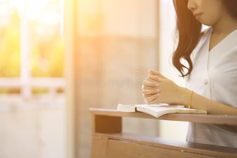 Kvinna som ber på en helig bibel i kyrkan för trobegrepp, andlighet och kristen religion arkivfoto