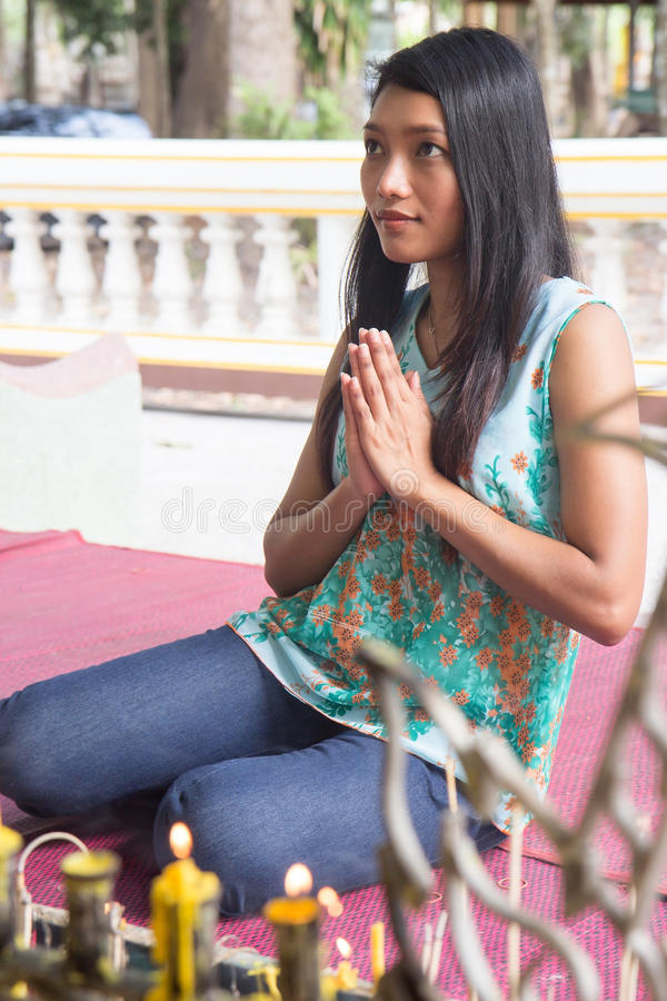 Kvinna som ber på en staty av Buddha royaltyfri bild