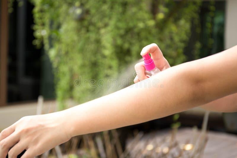 Kvinna som besprutar krypimpregneringsmedel på hud i trädgården arkivbilder