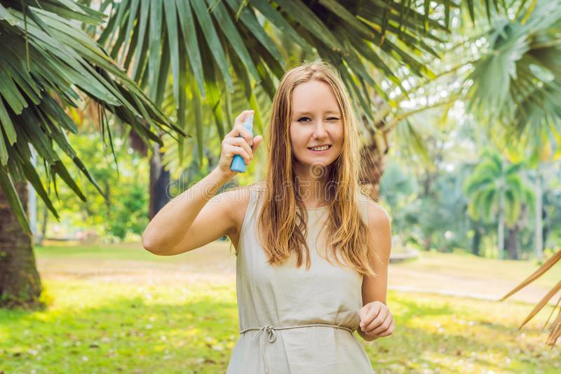 Kvinna som besprutar krypimpregneringsmedlet på utomhus- hud arkivbilder