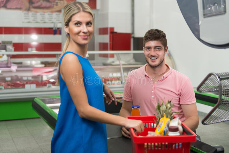 Kvinna som betalar för att shoppa på kontrollen med kortet royaltyfri bild