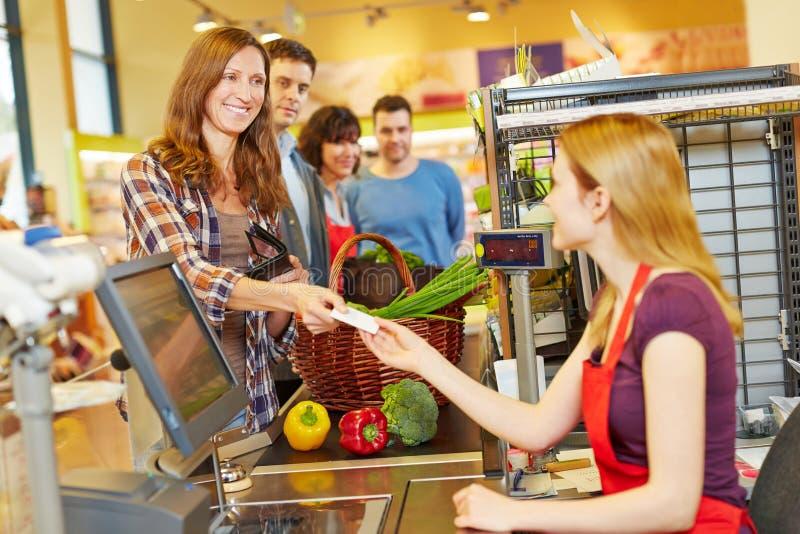 Kvinna som betalar med EC-kortet på supermarketkontrollen royaltyfri bild