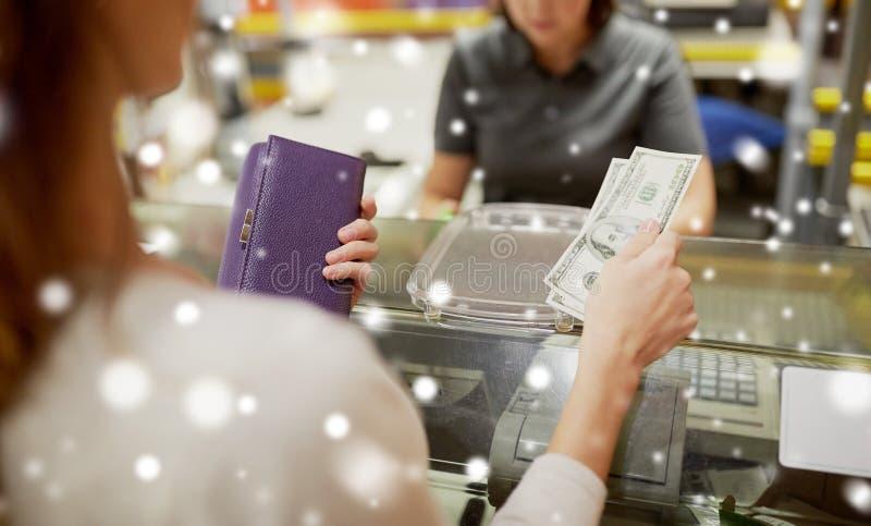 Kvinna som betalar pengar på lagerkassaapparaten royaltyfria bilder