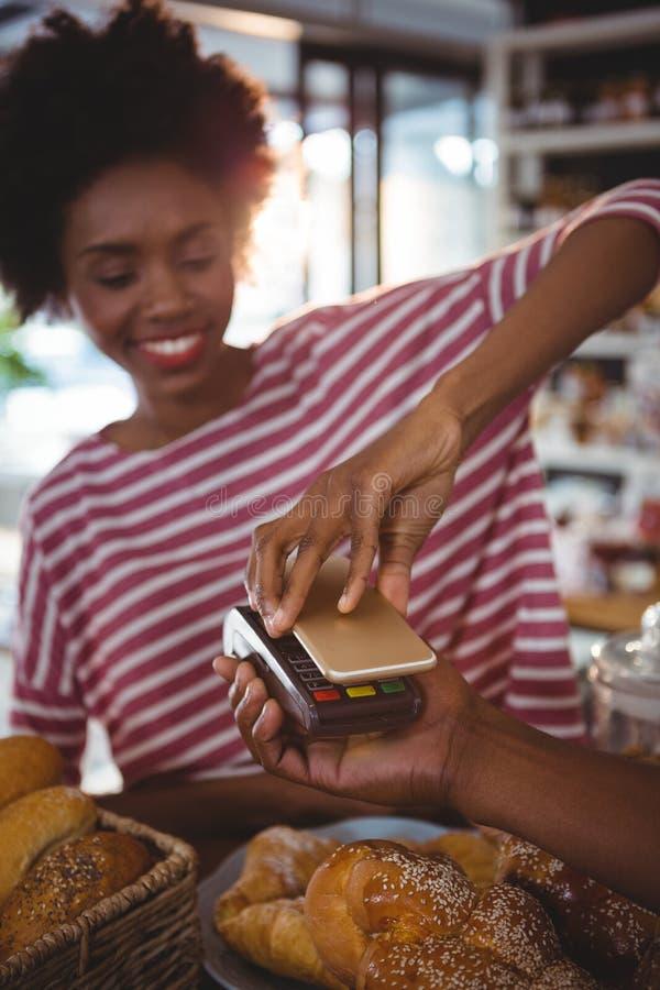 Kvinna som betalar räkningen till och med smartphonen genom att använda nfcteknologi royaltyfri bild