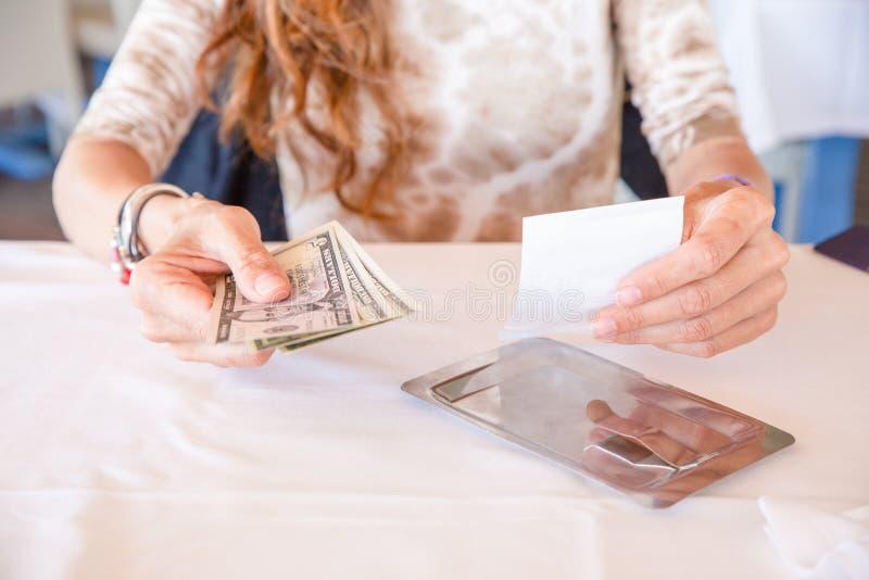 Kvinna som betalar restaurangräkningen med dollarsedlar royaltyfria bilder