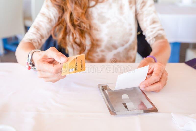 Kvinna som betalar restaurangräkningen med kreditkorten arkivbilder