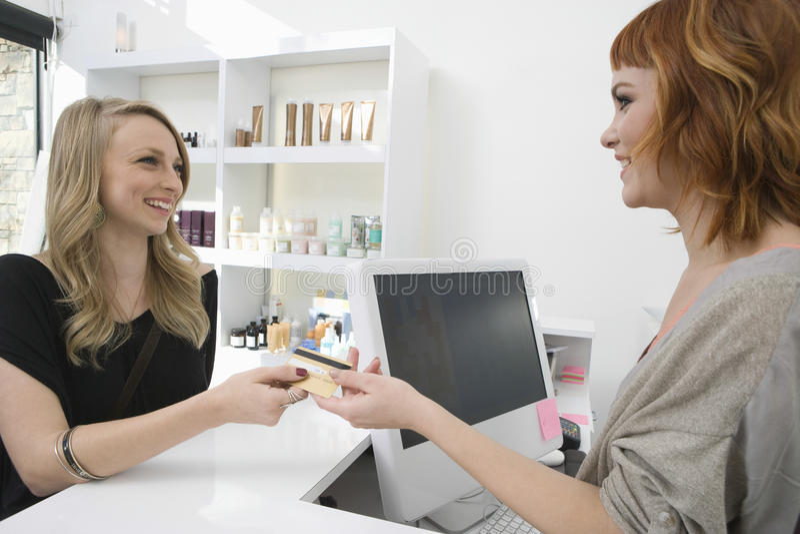 Kvinna som betalar till och med kreditkort på hårsalongen arkivfoto