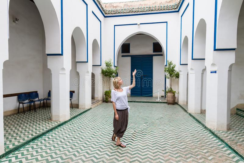 Kvinna som beundrar traditionell moroccan arkitektur i en av slottarna i medina av Marrakesh, Marocko arkivfoto
