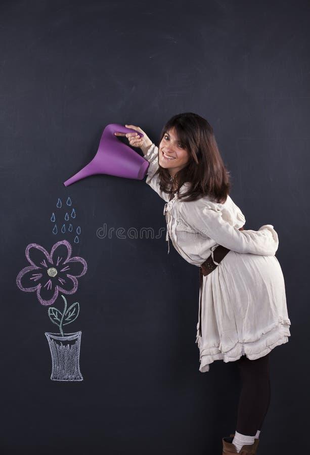 Kvinna som bevattnar en teckningsväxt royaltyfria foton