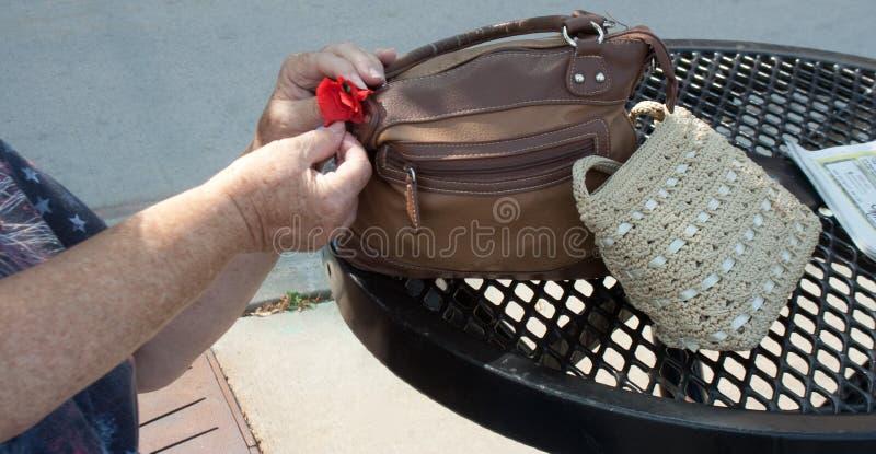 Kvinna som binder den röda vallmo på hennes handväska arkivfoto