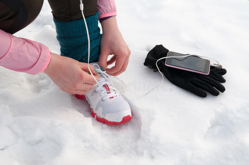 Kvinna som binder rinnande skor på snö arkivbilder