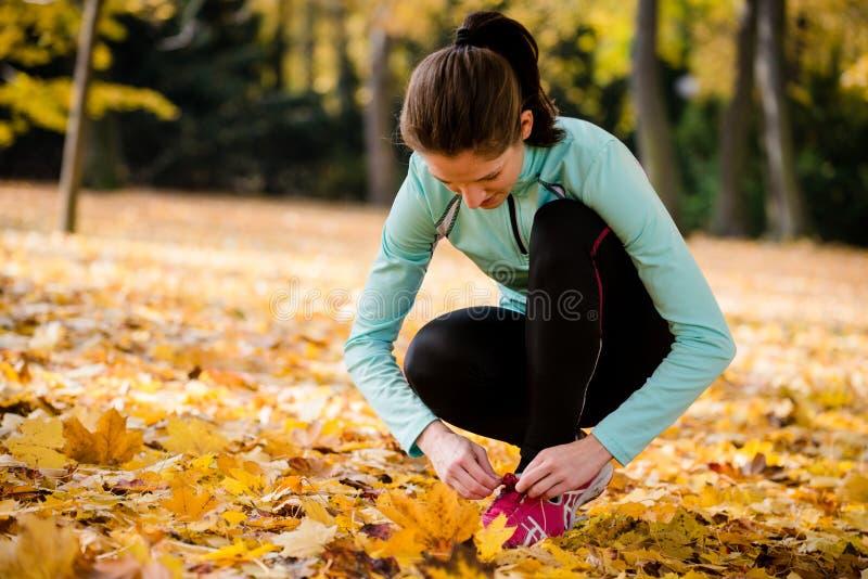 Kvinna som binder skosnöre - jogga i natur fotografering för bildbyråer
