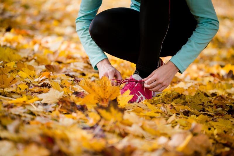 Kvinna som binder skosnöre - jogga i natur royaltyfri foto