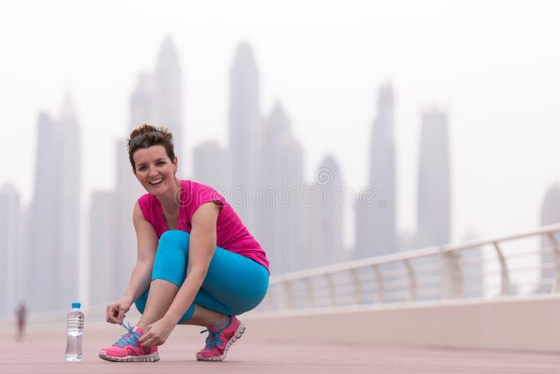 Kvinna som binder skosnöre på gymnastikskor royaltyfri foto