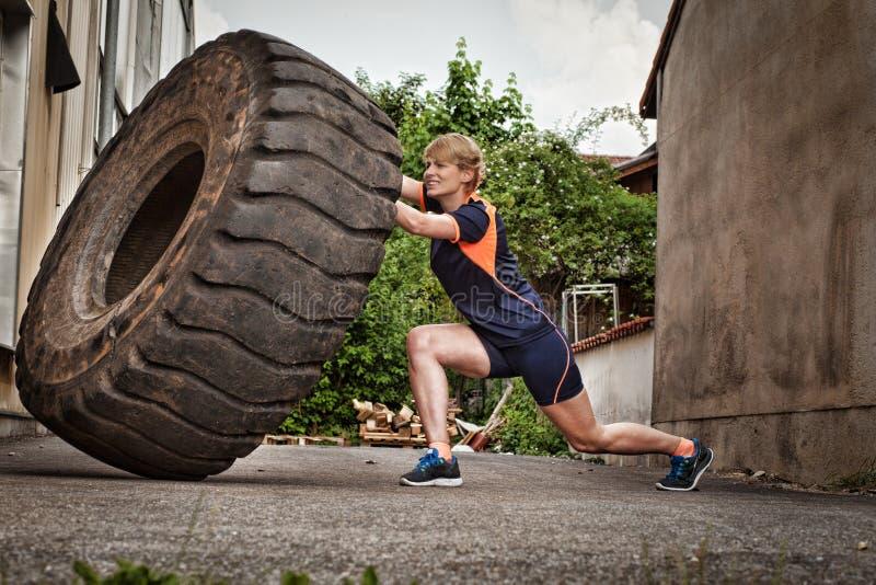 Kvinna som bläddrar en gummihjulcrossfitutbildning fotografering för bildbyråer