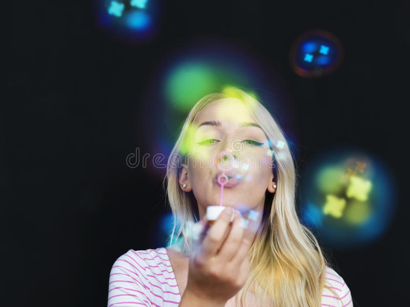 Kvinna som blåser bubblor på svart bakgrund royaltyfria foton
