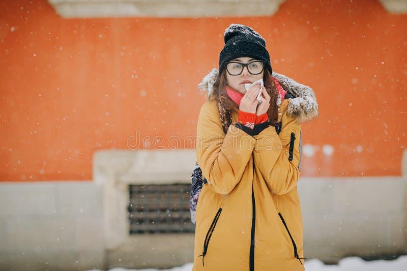 Kvinna som blåser hennes näsa i vinter Sjuk brunettkvinna royaltyfria bilder