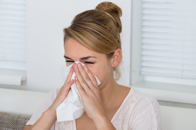 Kvinna som blåser näsan, medan lida från förkylning royaltyfri bild