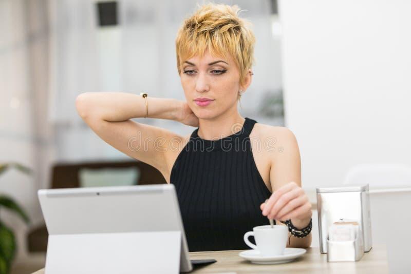 Kvinna som blandar hennes kaffe, medan genom att använda en dator i en stång royaltyfria bilder