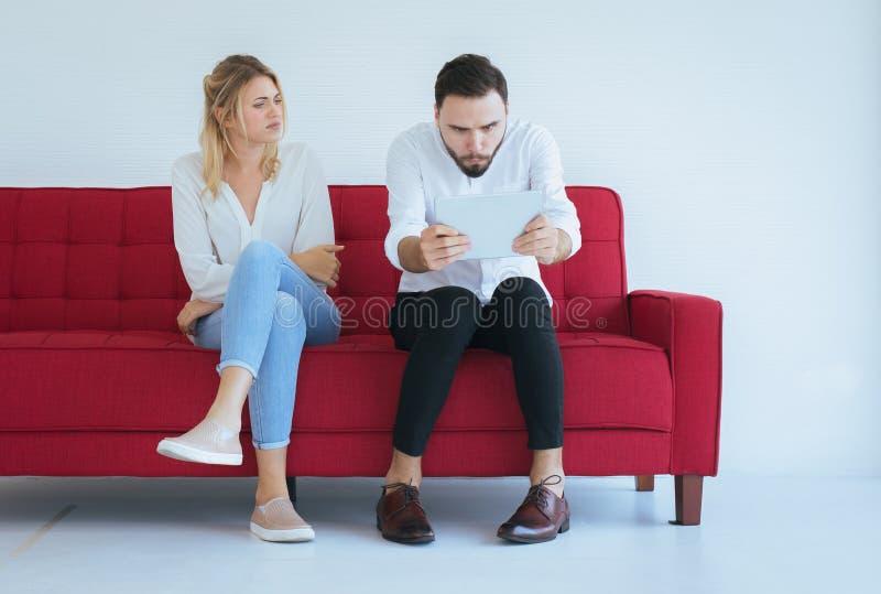 Kvinna som borras, och ignorerande till mannen som tillsammans sitter på soffan i vardagsrum, begrepp för familjfrågor arkivbilder
