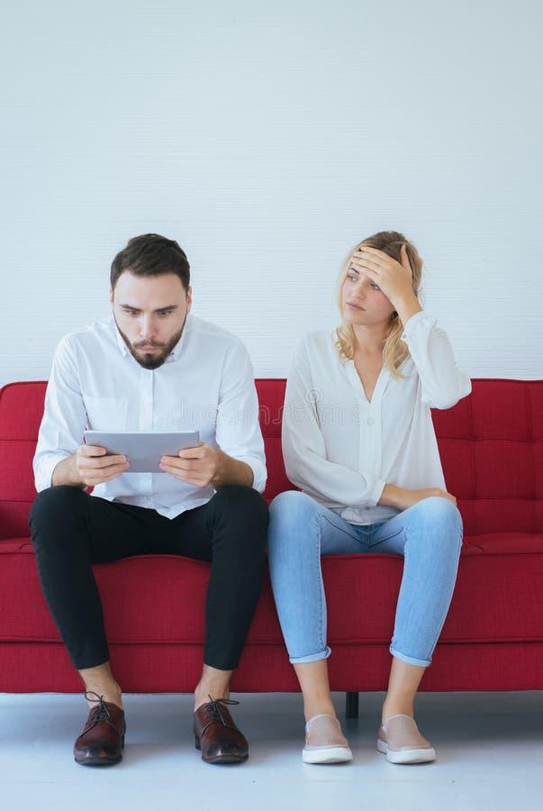 Kvinna som borras, och ignorerande till mannen som tillsammans sitter på soffan i vardagsrum, familjfrågor royaltyfri fotografi