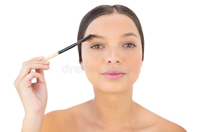 Kvinna som borstar hennes ögonbryn arkivbilder