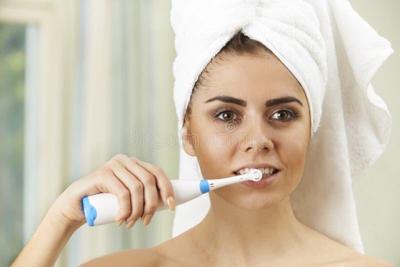 Kvinna som borstar tänder med den elektriska tandborsten i badrum royaltyfri bild