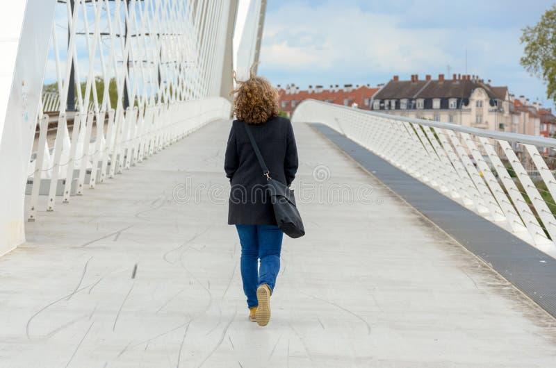 Kvinna som bort g?r ?ver en fot- bro arkivbilder