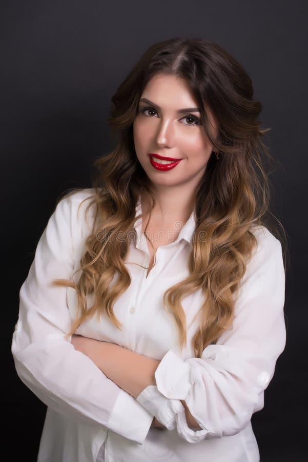 Kvinna som in camera poserar i den vita blicken för skjortasvartbakgrund med härligt smink arkivfoto