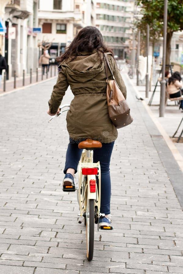 Kvinna som cyklar ner gatan royaltyfri fotografi