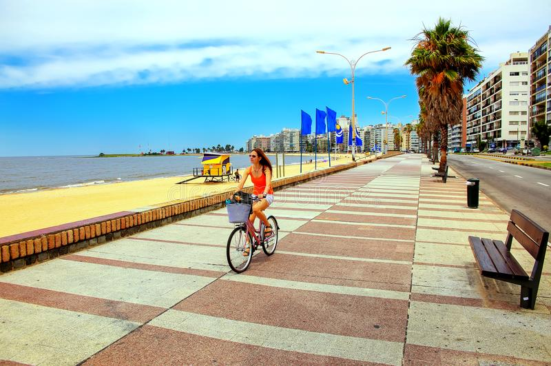 Kvinna som cyklar på boulevarden längs den Pocitos stranden i Montevideo, royaltyfri fotografi