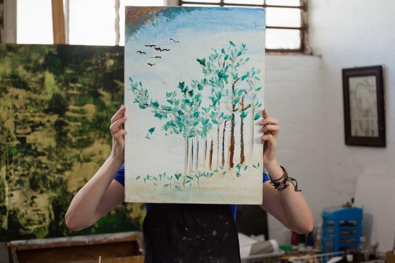 Kvinna som döljer hennes framsida bak målning arkivfoto