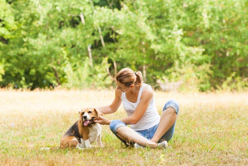 Kvinna som daltar hennes hund som sitter utomhus på gräs arkivfoton
