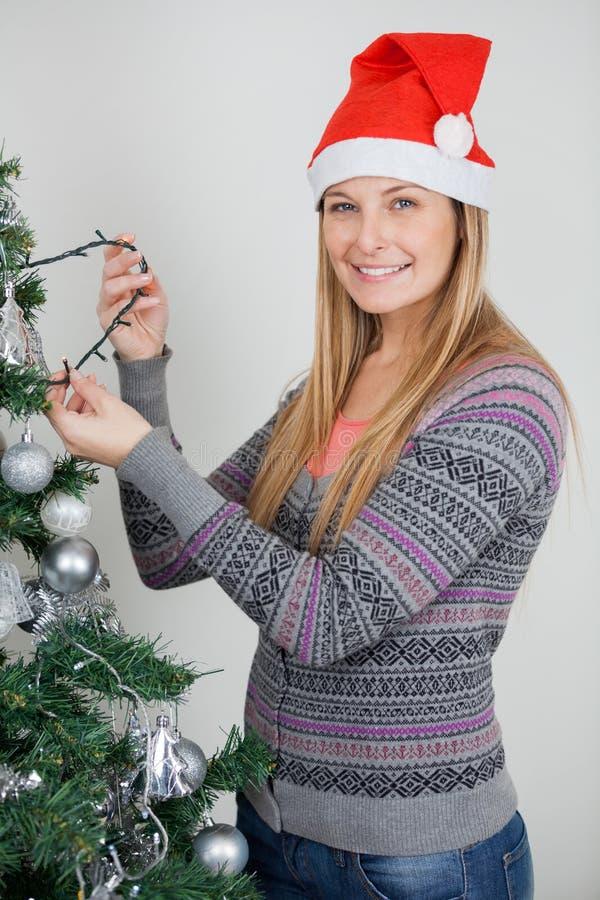 Kvinna som dekorerar julgranen med felika ljus arkivbild